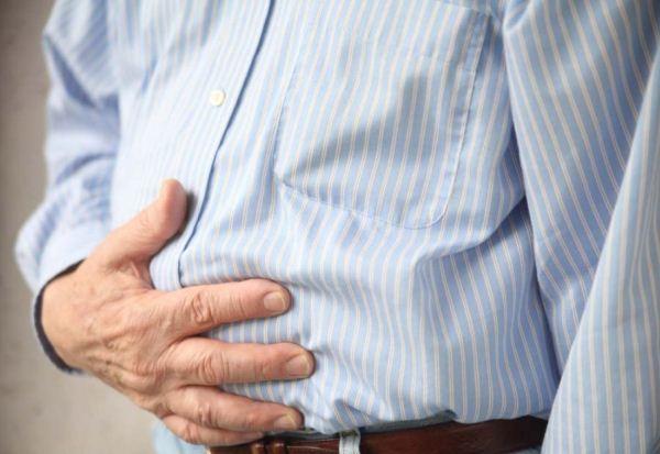 Csíkos inget vieslő idősebb férfi kezét a gyomrára szorítja, valószínűleg gyomorfájdalma van.