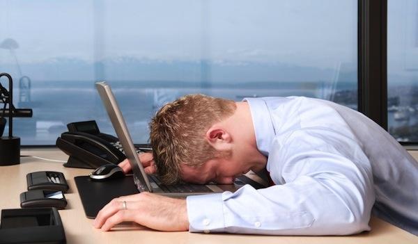 Fiatal üzletember irodájában fáradtan, a laptopjára bukva pihen.