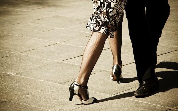 Tangót tácoló pár lába, a csinos hölgyön sikkes cipő és neccharisnya.