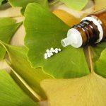 Ginkgo biloba levelei, rajta homeopátiás golyókkal teli üvegcse, az egyik levélen pár szem gyógyszer.