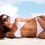 Csinos, fiatal nő napszemüvegben, fehér bikiniben egy homokos tengerparton napozik.