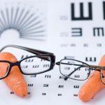 Vicces kép, melyen a látás fontosságát szimbolizálják két sárgarépára helyezett szemüveggel, a háttérben látásvizsgálatnál hazsnálatos ábrákkal.