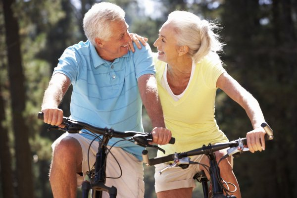 Idősebb házaspár szorosan egymás mellett biciklizik, mosolyognak egymásra.