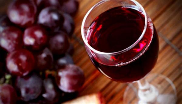 Üvegpohárban lévő vörösbor, mellette nagy fürt szőlő.