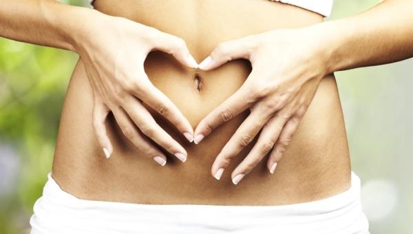 Fiatal nő köldöke köré ujjaival szívet formál.