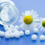 Homeopátiás golyócskák kiszórva egy üvegcséből, mellettük kamillavirág.