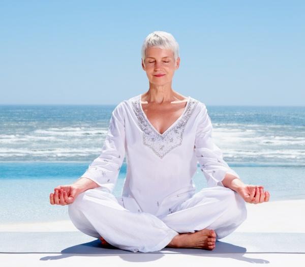 Idősebb hölgy jógázva meditál a tengerparton.