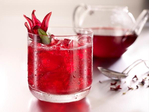 Hibiszkuszból készült frssítő tea jégkockákkal üvegpohárban, háttérben a teáskanna.