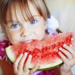 Kék szemű kislány egy nagy szelet görögdinnyét majszol.