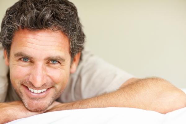 Jóképű, 40 év körüli férfi mosolyog a kamerába, állát kezére támasztva.