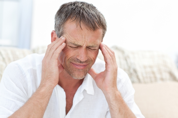 Erős fejfájásban szenvedő középkorú férfi fogja halántékát, arca fájdalmat tükröz.