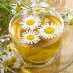 Kamillatea üvegcsészében, benne kamillavirágok, mellette az egész növény.