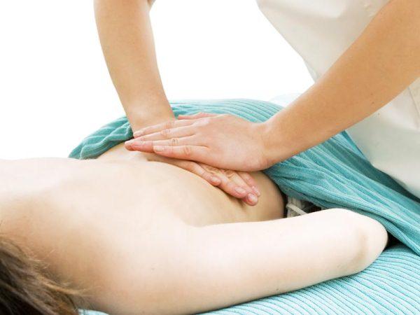 Oszteopata keze munka közben egy hölgy hátán.