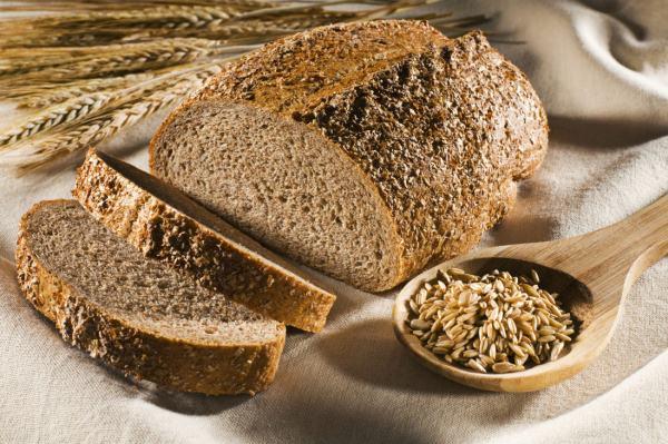 Teljes kiőrlésű kenyér szeletelve, mellette búzakalász és fakanálban magok.