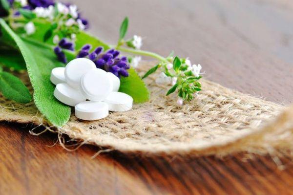 Schüssler-só pasztilák színes gyógynövényekkel együtt egy háncsdarabon.