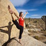 Jógázó nő egy sziklatömb előtt a sivatagban.