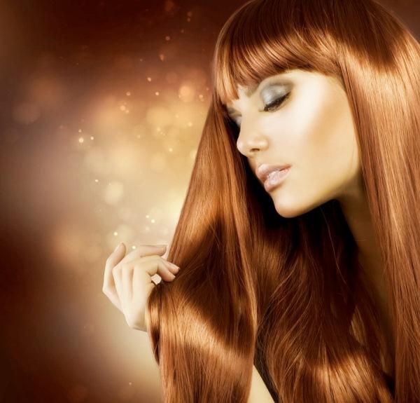 Hosszú, vörösbarna hajú lány fotója, a háttérban apró fények.