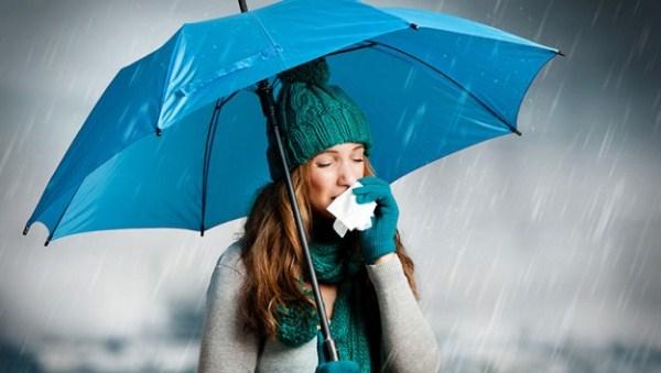 Sapkát és kesztyűt viselő lány orrát törli szakadó esőben egy kék esernyő alatt.