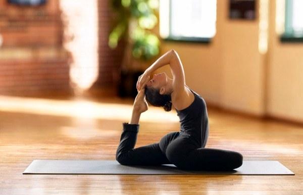 Jógagyakorlatot végző nő jógamatracon egy napsütötte szobában.