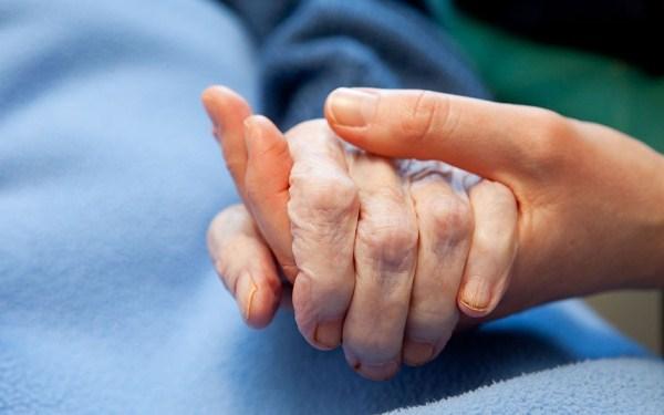 Fekvő, kék pléddel betakart idős néni kezét fogja egy fiatal kéz.