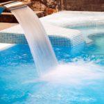 Wellnesshotel medencéje vízzuhataggal.