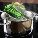 Forró vízzel teli lábasból vesznek ki szűrőkanállal egy adag zöldbabot.