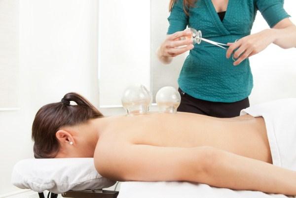 Köpölyöző poharakat melegít egy terapeuta, melyet egy nő hátára helyez fel.