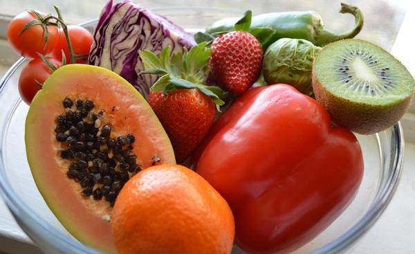 Sok C-vitamint tartalmazó zöldségek és gyümölcsök üvegtálon: kivi, piros paprika, eper, paradicsom, kelbimbó, narancs, lila káposzta és egy egzotikus gyümölcs félbevágva.