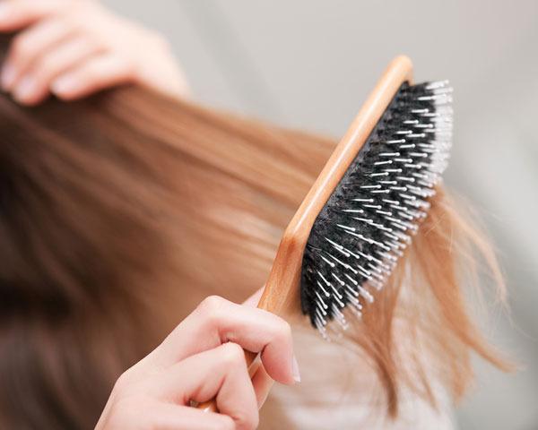 Hosszú hajú lány hajkefével a haját fésüli.