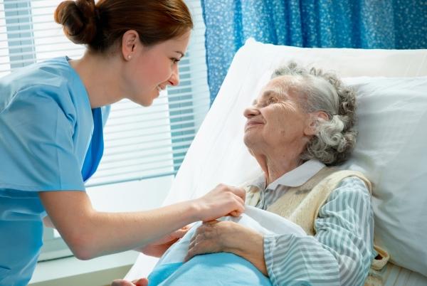 Ágyban fekvő idős nénin igazítja a takarót egy fiatal, mosolygós nővérke.