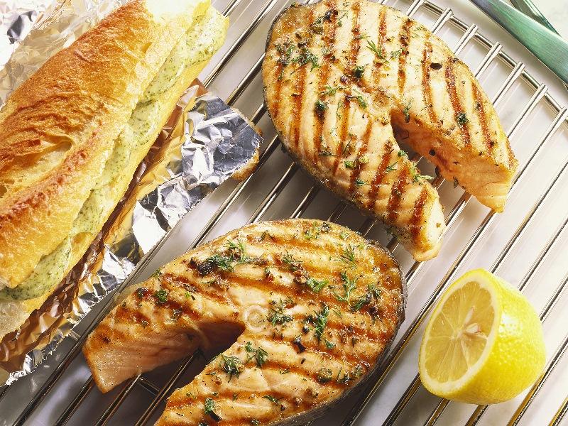 Grillezett halszeletek rácson, mellettük félbevágott citrom és ropogós kenyér.