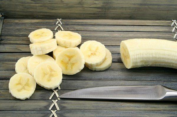 Két részre vágott banán, egyik fele egészben hagyva, másik apró szeletkékre vágva, mellette egy kés.