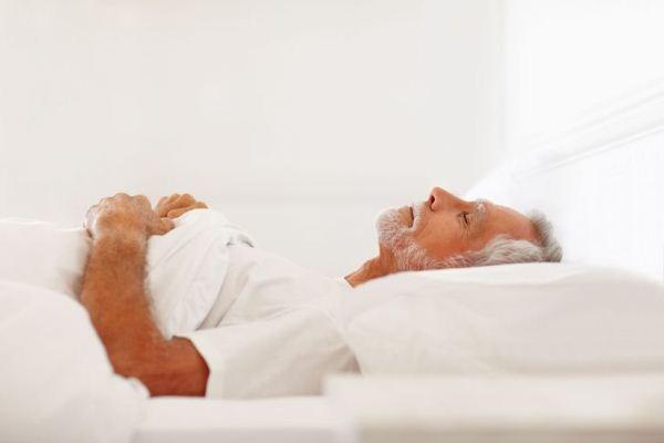 Ősz hajú férfi fehér pólóban, fehér ágyneműben alszik.