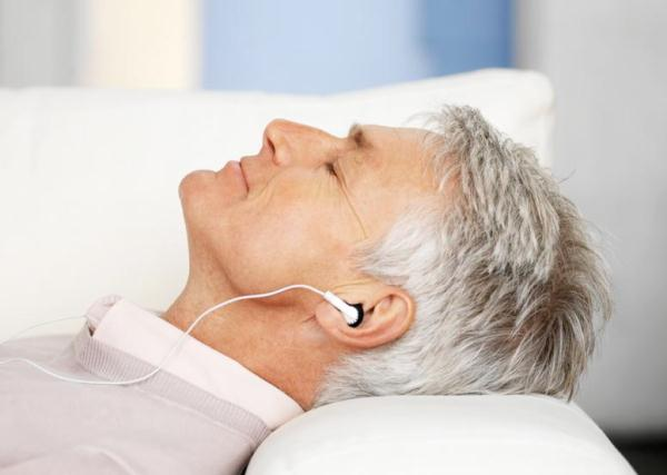 Ősz hajú idősebb férfi kanapén fekve fülhallgatóján keresztül zenét hallgat.