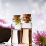 Rózsaszínű dália és a belőle készült kivonatok kicsi üvegcsékben, a háttérben egy barna tál tele hasonló virágokkal.