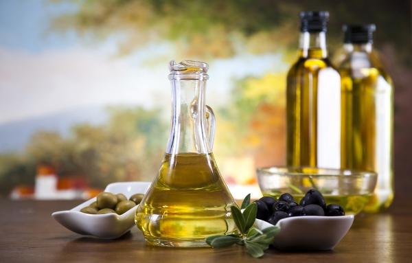 A kép előterében friss fekete és zöld olajbogyó, közöttük üvegkancsóban olívaolaj, a háttérben palackozott növényi olajak és egy vidéki táj elmosódott képe.