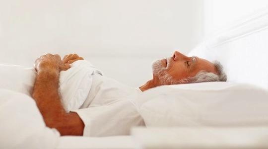 Felfekvés elleni matracot használó idős férfi.