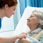 Felfekvésben szenvedő idős beteg nő ápolása felfekvés elleni matrac segítségével.
