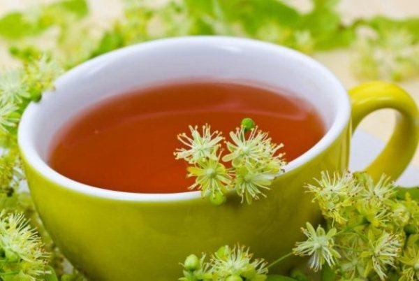 Hársfatea zöld csészében, mellette a hársfa virágai.
