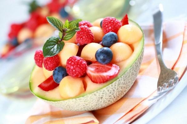 Félbevágott sárgadinnyében színes gyümölcsmix eperrel, málnával és áfonyával.
