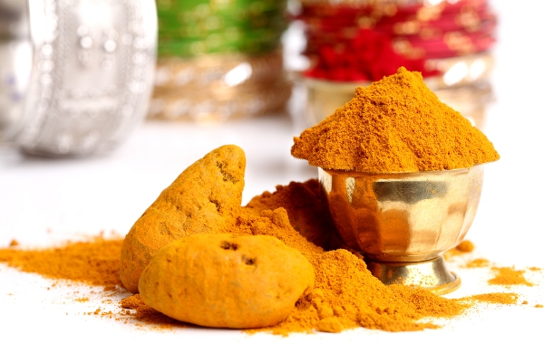 A kurkuma hatóanyaga, a kurkumin egy sárga fém edénykében, por alakban.