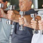 Ezüst színű kézisúlyzókat emelnek egymás mellett állva mosolygós, idősebb emberek.