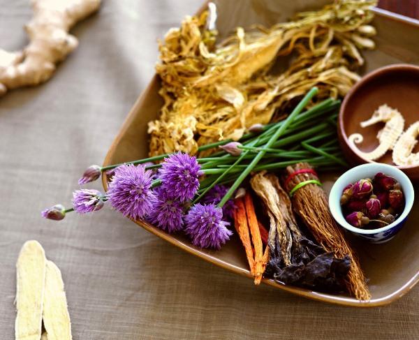 Gyógynövények, szárított gyökerek és virágok egy tálon elhelyezve.