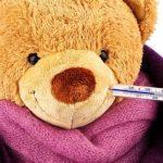 Teddy mackó szájában lázmérő, nyakán egy pink és egy bordó sál.