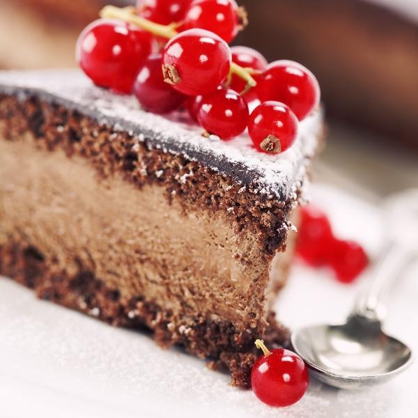 Csokoládés krémmel töltött torta egyik szeletkéje, a tetején porcukor és friss ribizli.