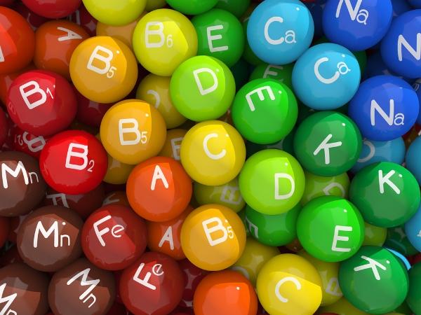 Színes cukorkákhoz hasonlító golyók, feliratozva a vitaminok és az ásványi anyagok jeleivel.