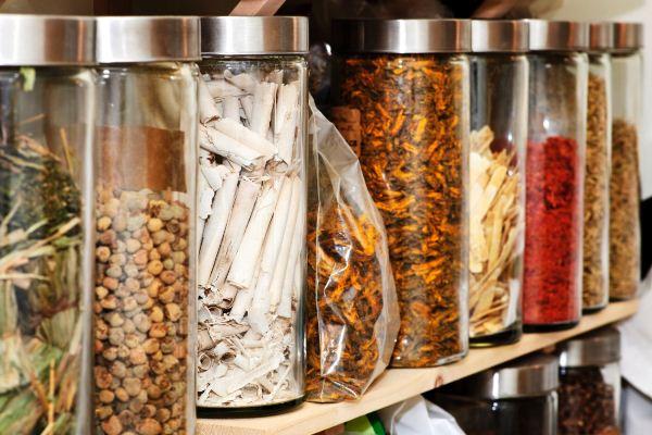 Hagyományos kínai gyógyszerek növényi alapanyagai egymás mellé állítva a polcon átlátszó üvegedényben.