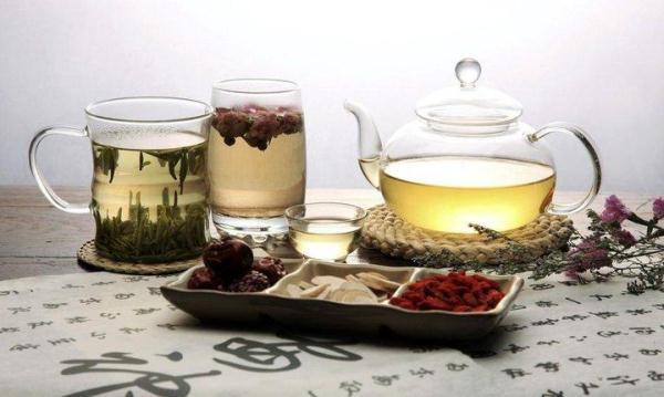 Kínai gyógynövényekből készült teák különféle poharakban, a terítőn kínai írásjelek.