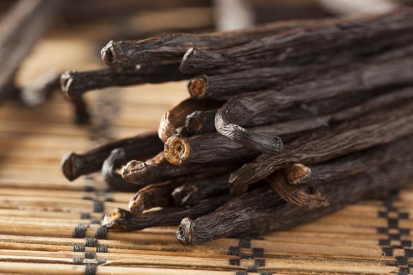 Vaníiliarudak egy csokorba kötve, bambusz alátétre fektetve.
