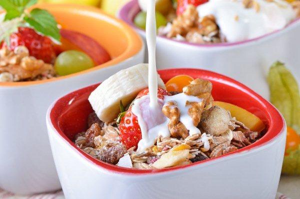 Színes belsejű kerámia tálkákban frissen készített müzlire öntenek tejet, a pohár tetején epr, banán, dió, magvak, zabpehely.